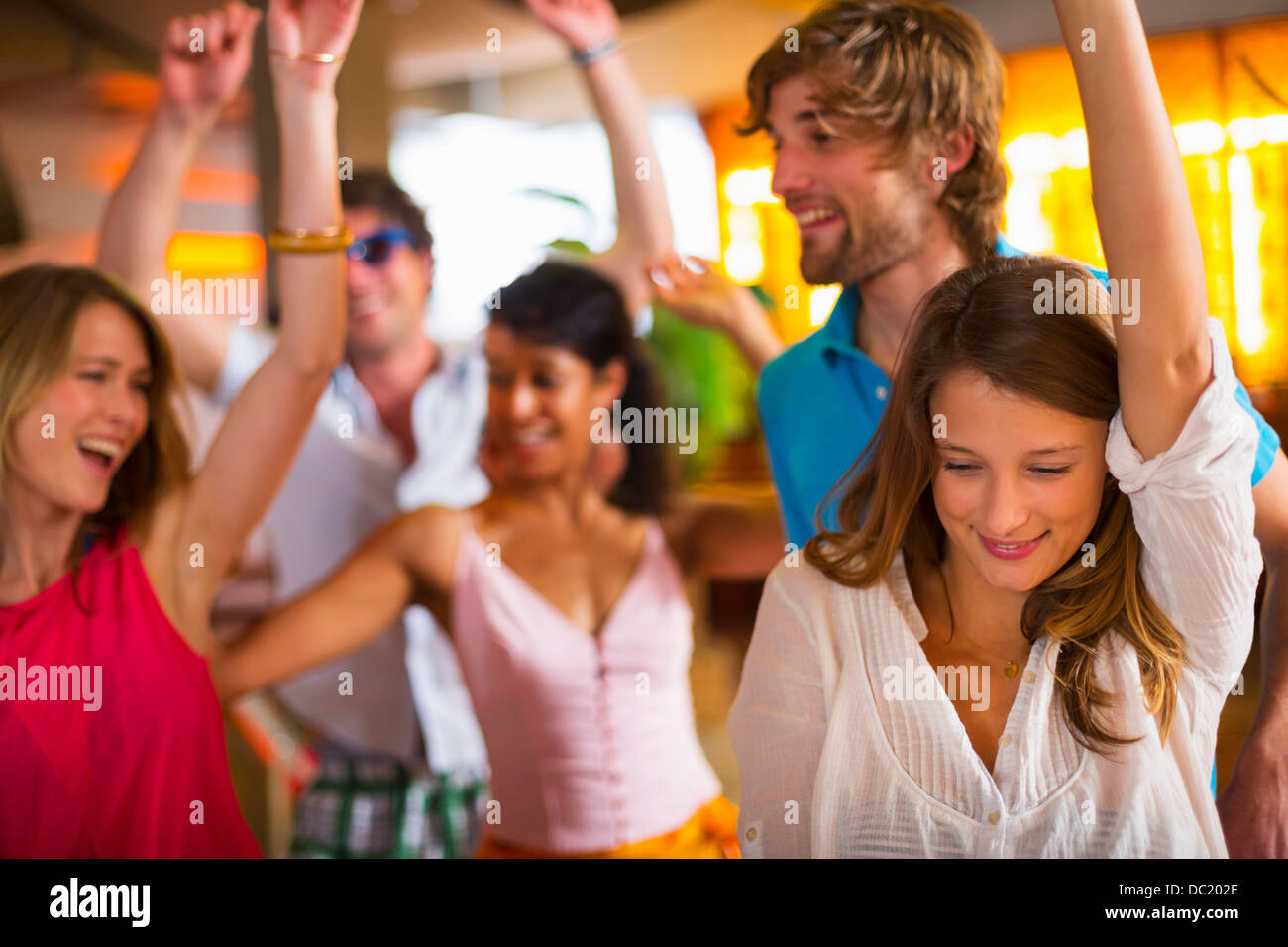 Friends dancing with arms up in bar - Stock Image
