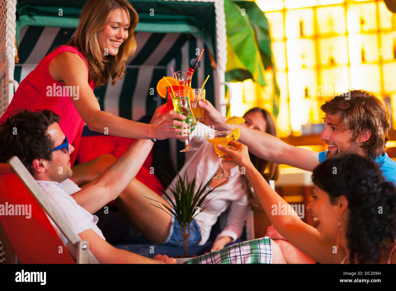 Group of friends with cocktails at indoor beach party - Stock Image