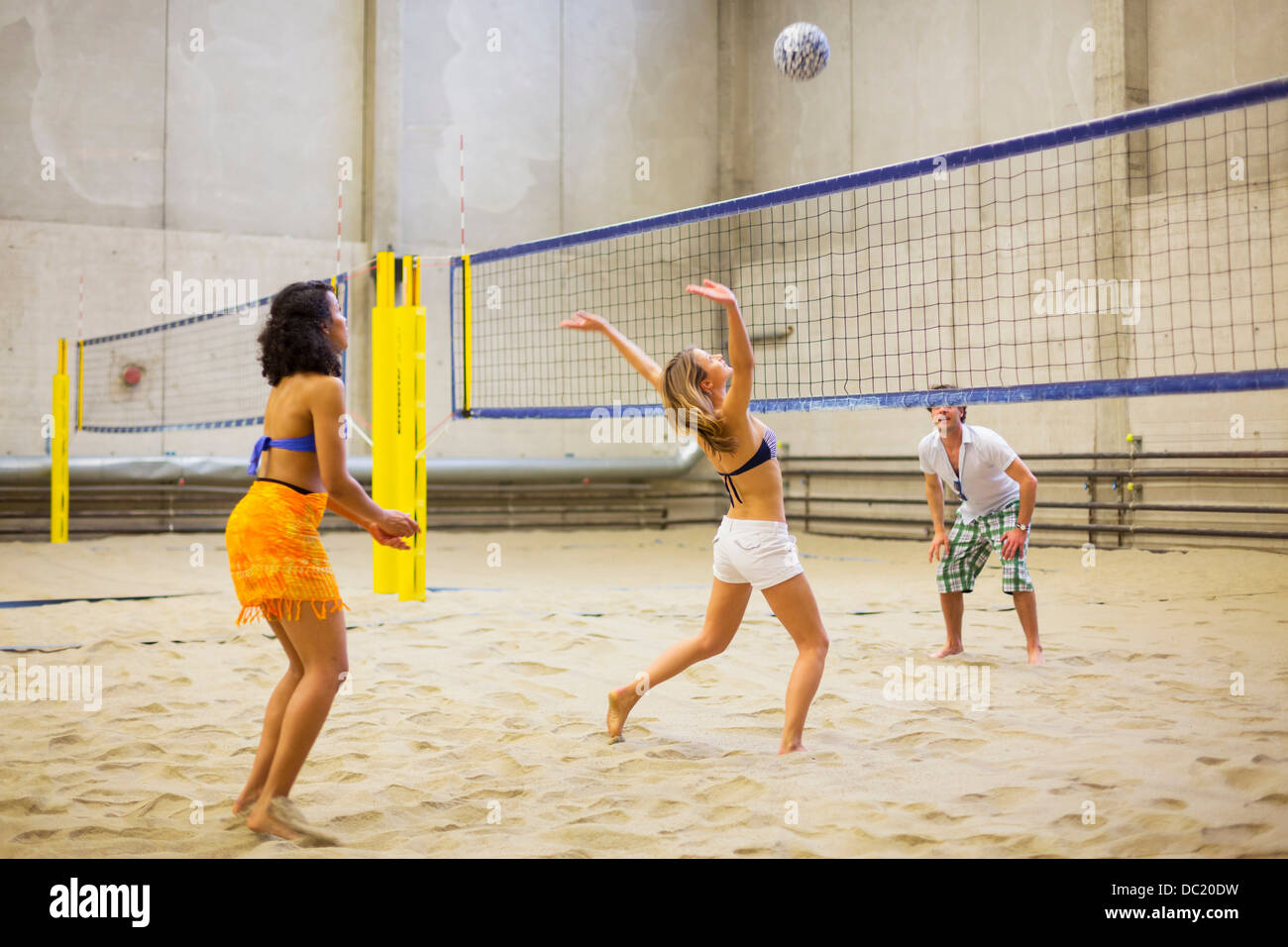 Friends playing indoor beach volleyball - Stock Image
