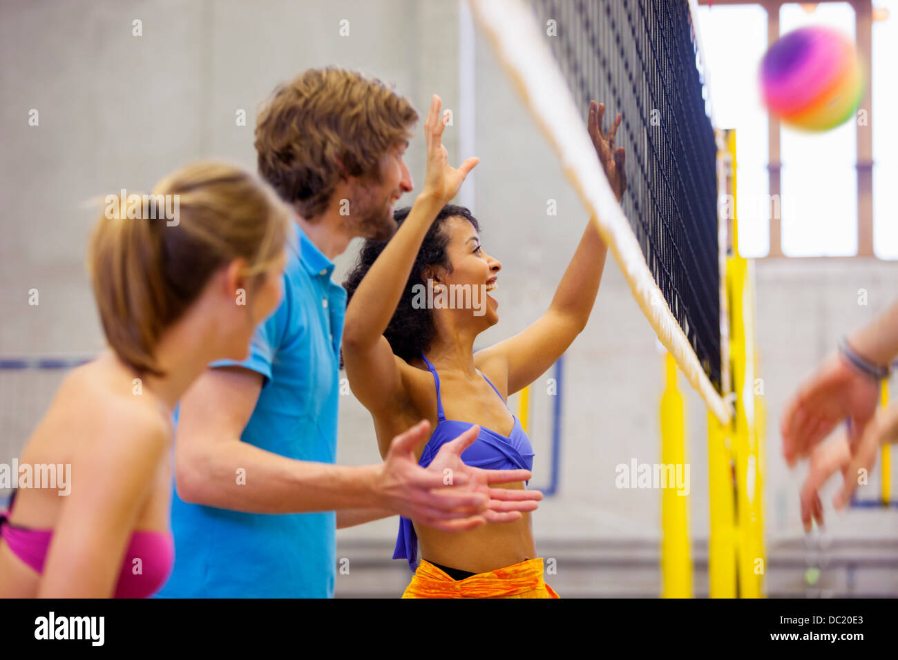 Friends enjoying indoor beach volleyball - Stock Image