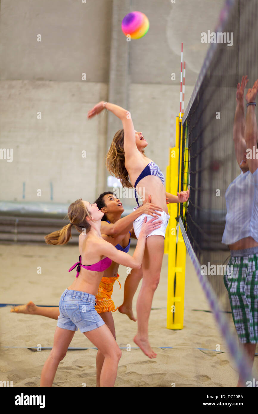 Friends playing beach volleyball at sports centre - Stock Image