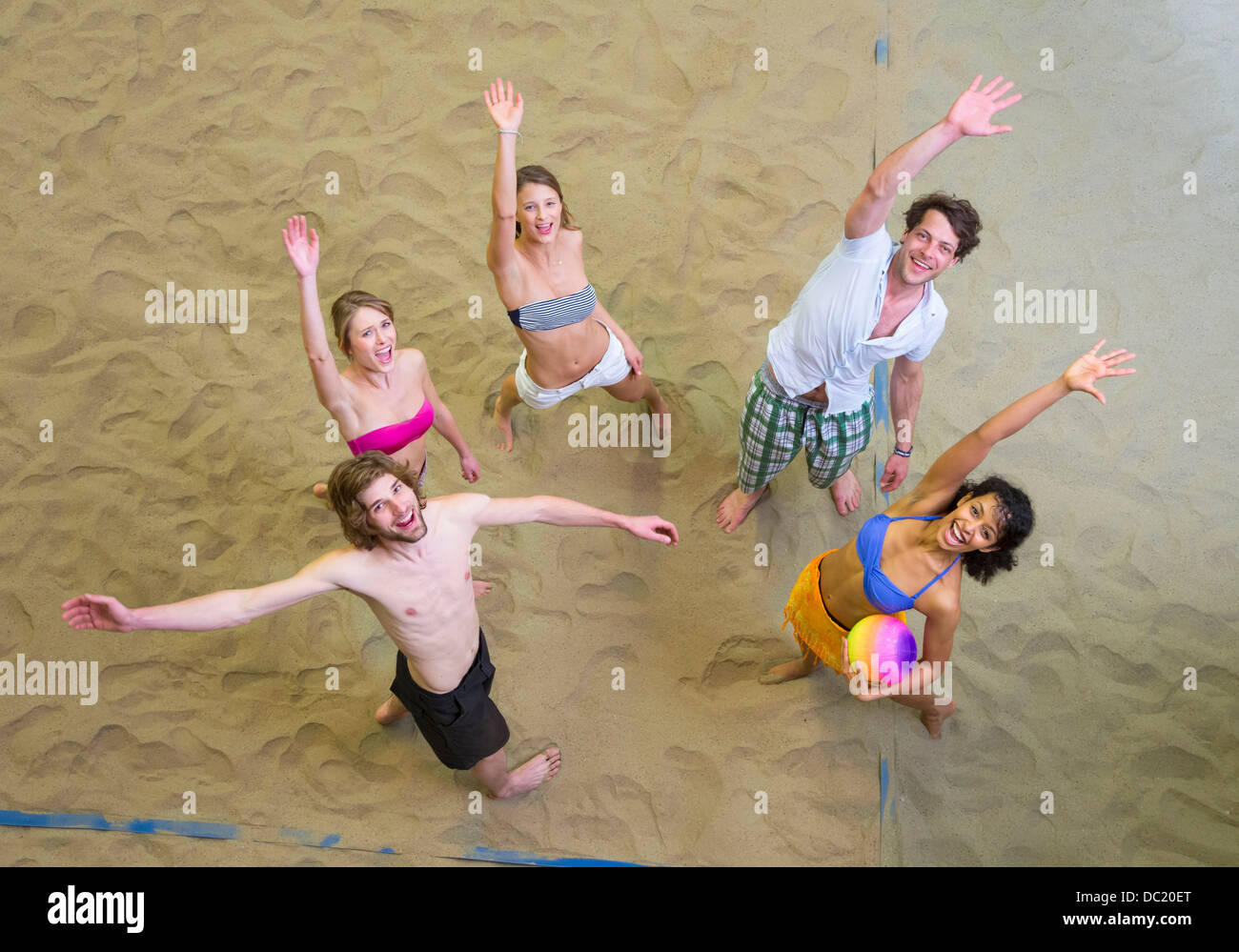 Aerial view of friends waving at indoor beach volleyball - Stock Image