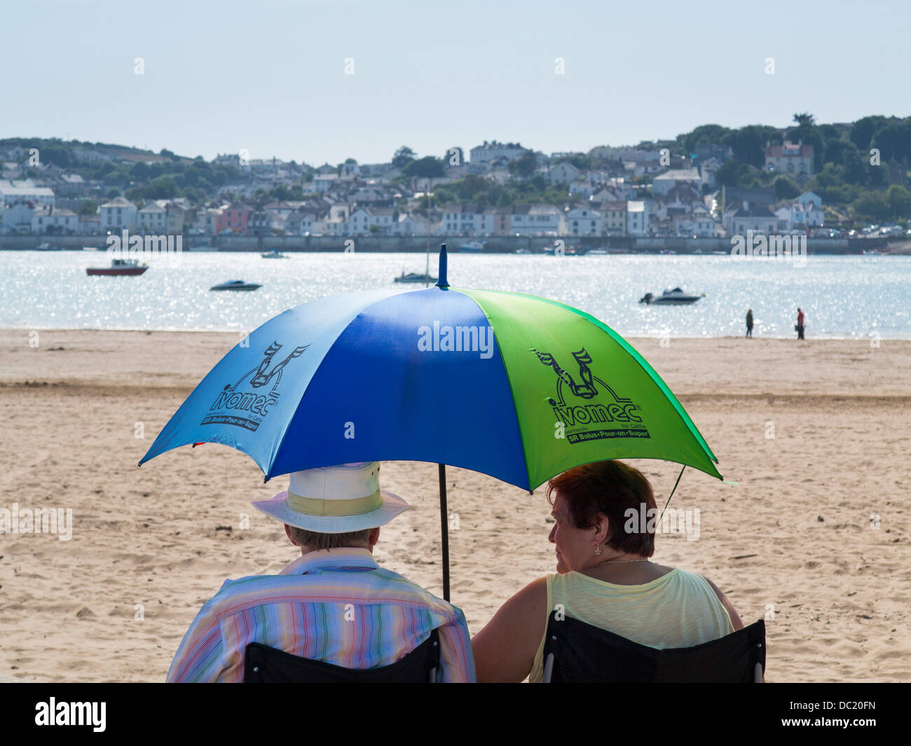 Couple sitting on Instow beach using an umbrella as a parasol, North Devon, England - Stock Image