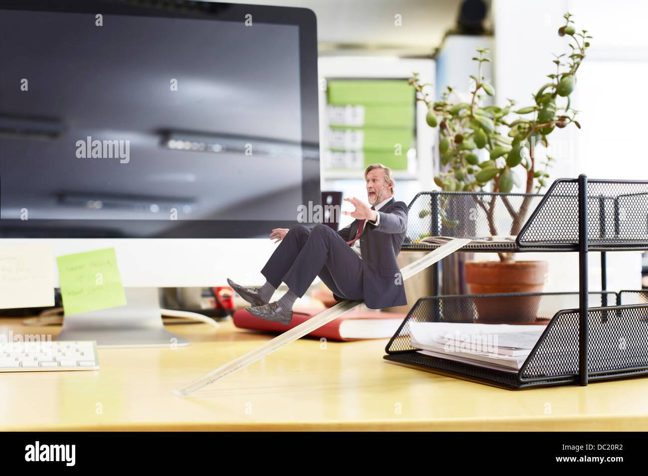 Mature businessman sliding down ruler on oversized desk - Stock Image
