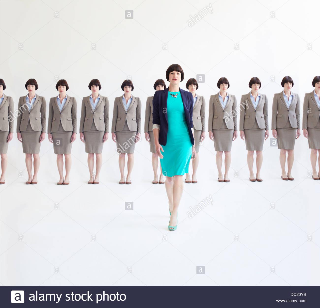 Businesswoman walking away from line of identical women, studio shot - Stock Image