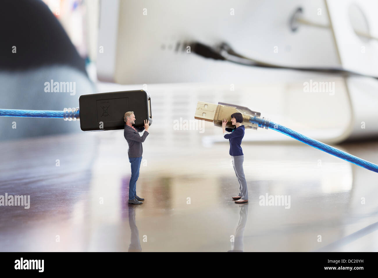 Office colleagues holding large computer cables on oversized desk Stock Photo