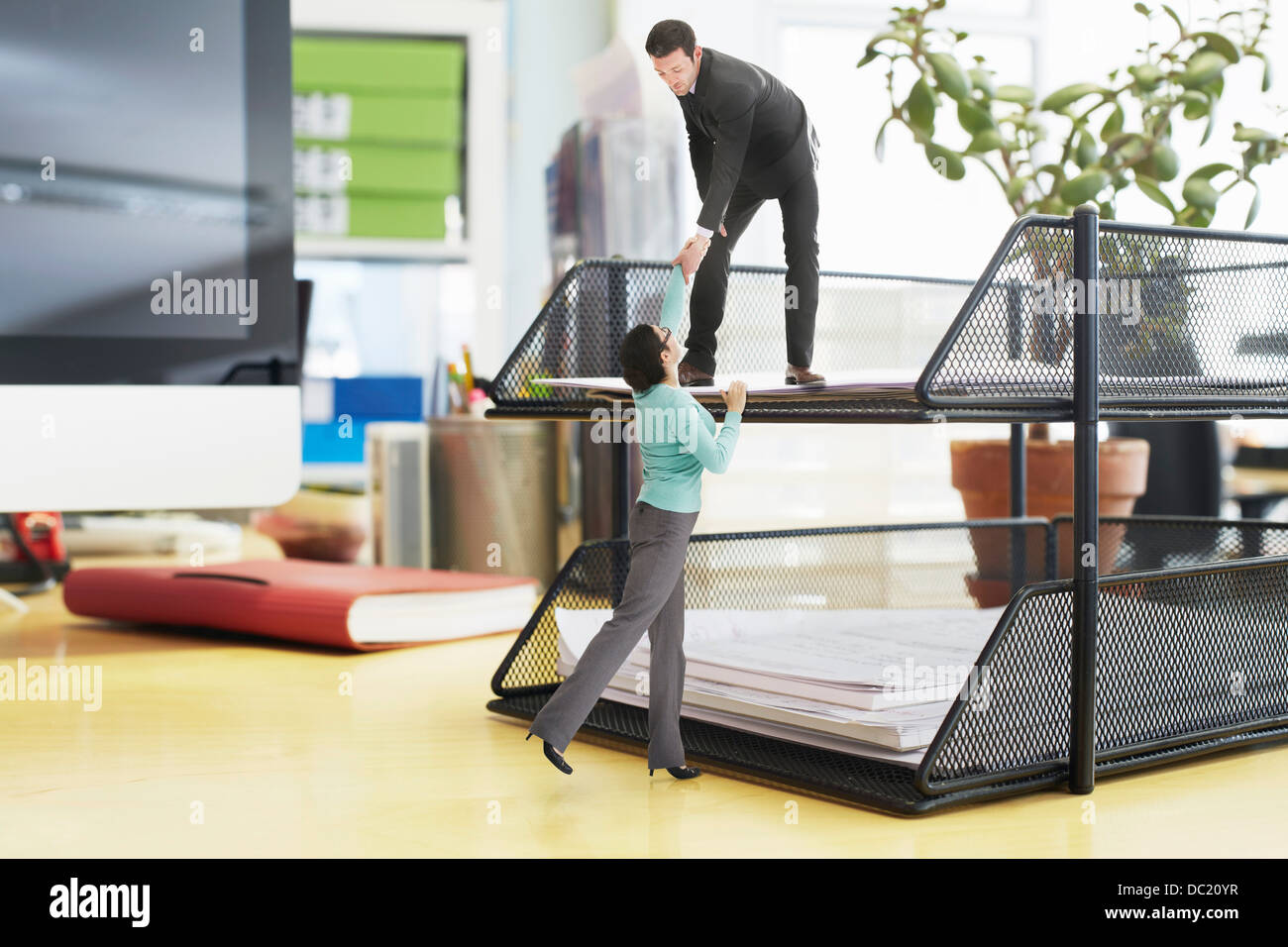 Businessman offering helping hand to colleague on large inbox on oversized desk - Stock Image