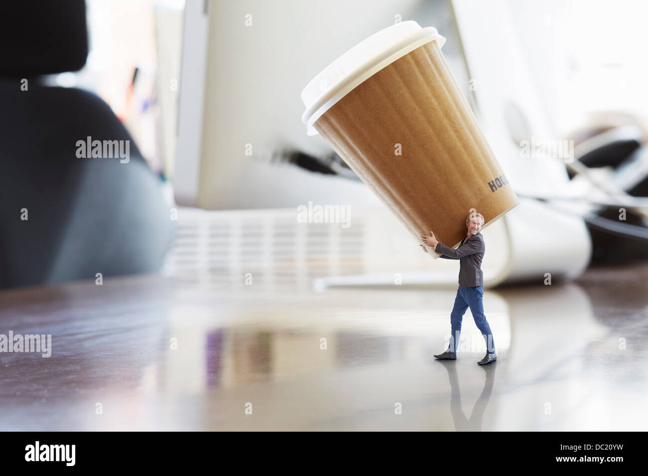 Mature businessman carrying large disposable cup on oversized desk - Stock Image