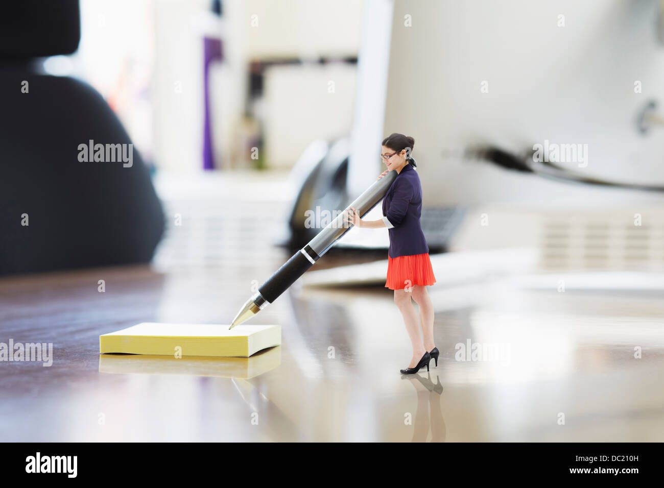 Businesswoman writing on large adhesive label on oversized desk - Stock Image