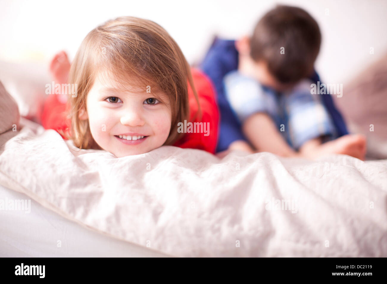 Portrait of young girl smiling and brother sulking - Stock Image