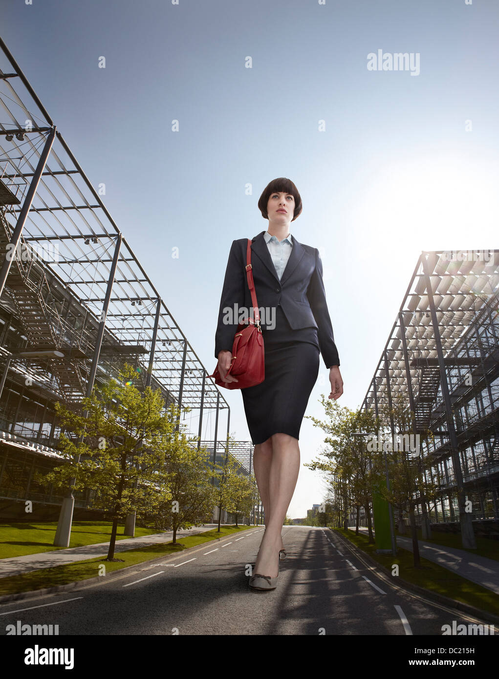 Oversized businesswoman walking on road, low angle view - Stock Image