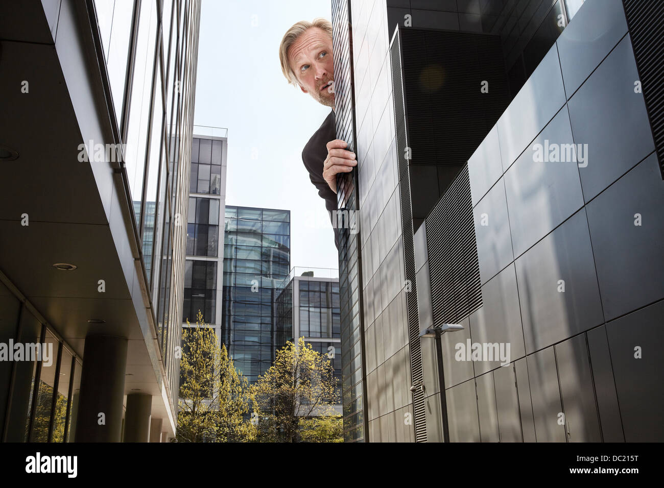 Oversized businessman peering from behind skyscrapers, low angle view - Stock Image