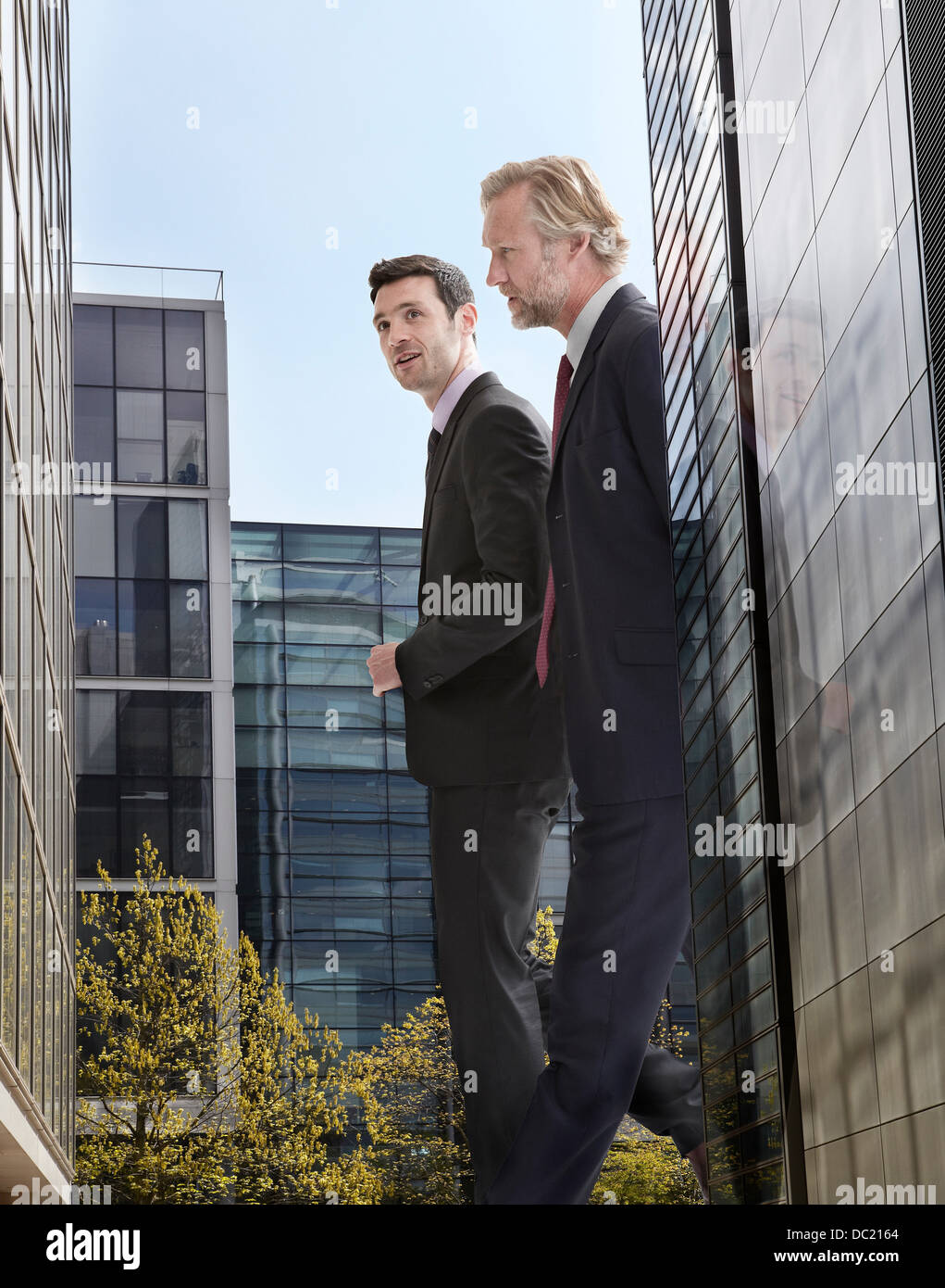 Oversized businessmen walking amongst skyscrapers, low angle view - Stock Image