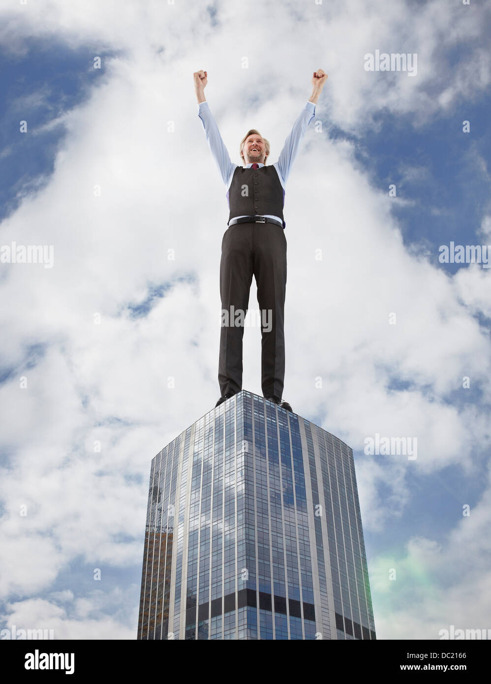 Oversized businessman cheering on skyscraper, low angle view - Stock Image