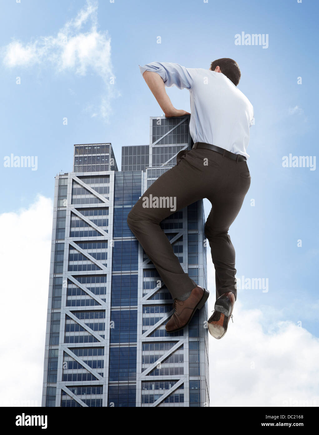 Oversized businessman climbing skyscraper, low angle view - Stock Image
