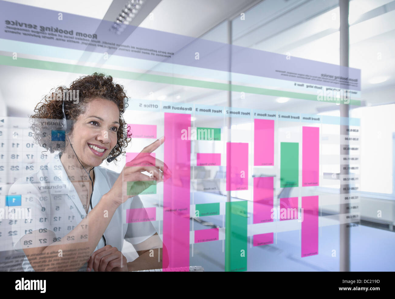 Receptionist booking meeting rooms with interactive screen Stock Photo