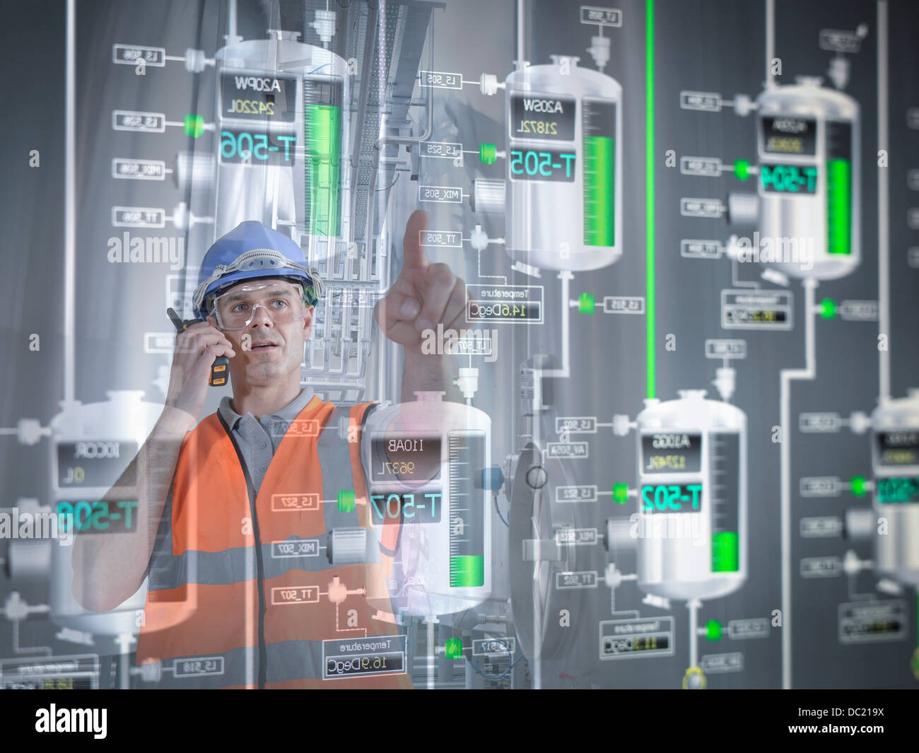 Factory supervisor monitoring product levels on interactive display Stock Photo