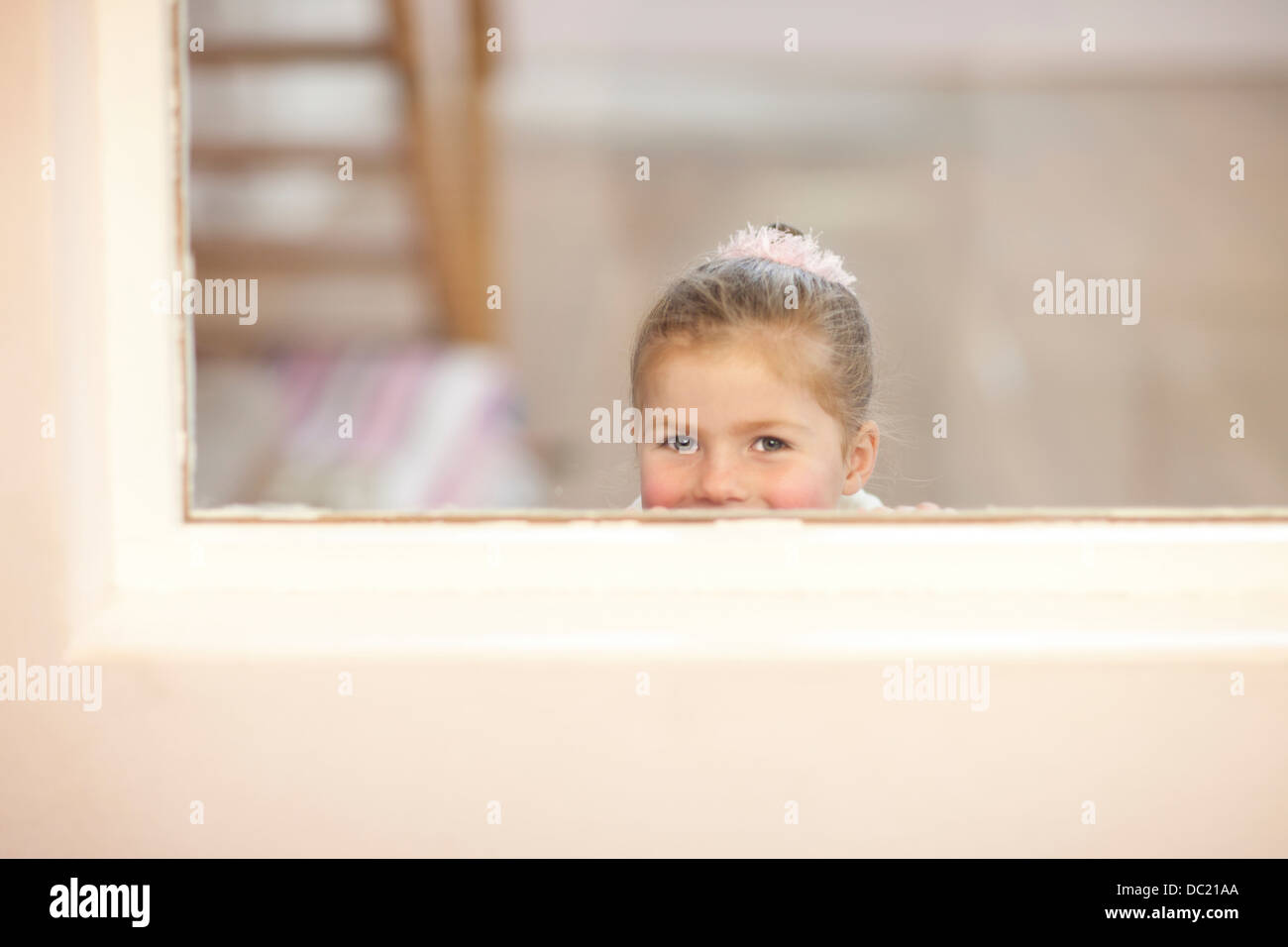 Young girl looking through window at ballet class - Stock Image