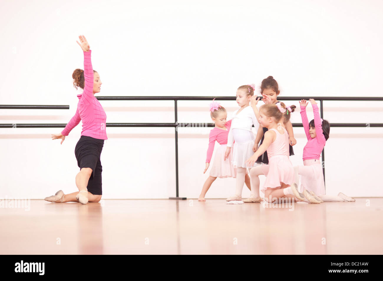 Teacher demonstrating to a group of young ballerinas Stock Photo