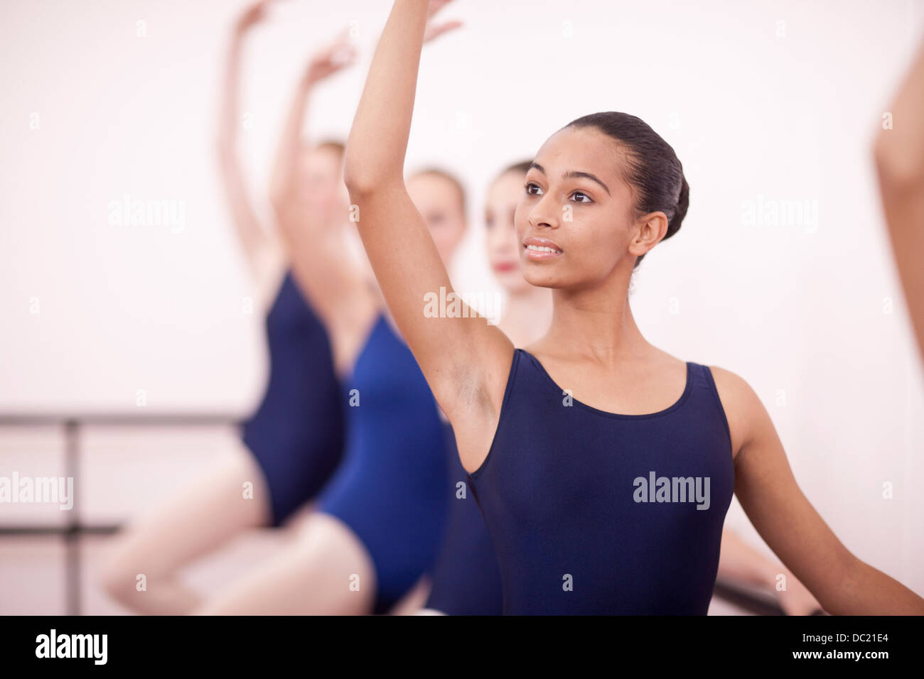 Row of teenage ballerinas with arms up - Stock Image