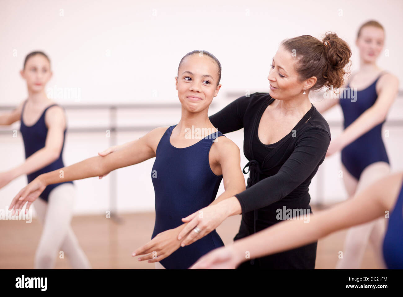 Teacher adjusting arms of shy teenage ballerina - Stock Image