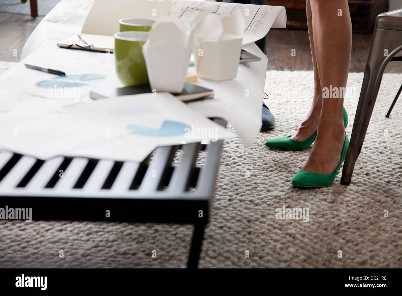 Mature woman in green high heels in office, low section - Stock Image