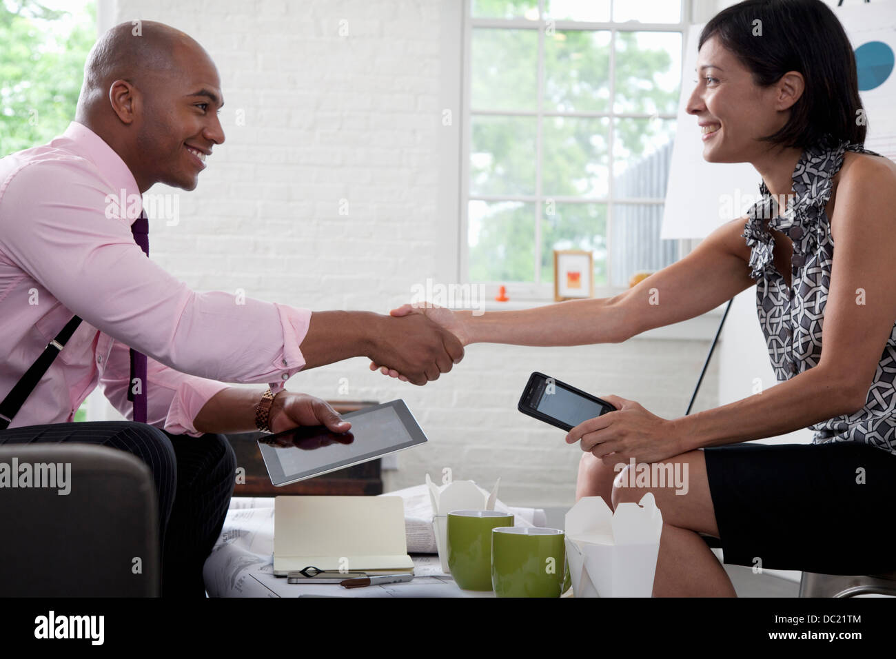 Office colleagues shaking hands in meeting, smiling - Stock Image
