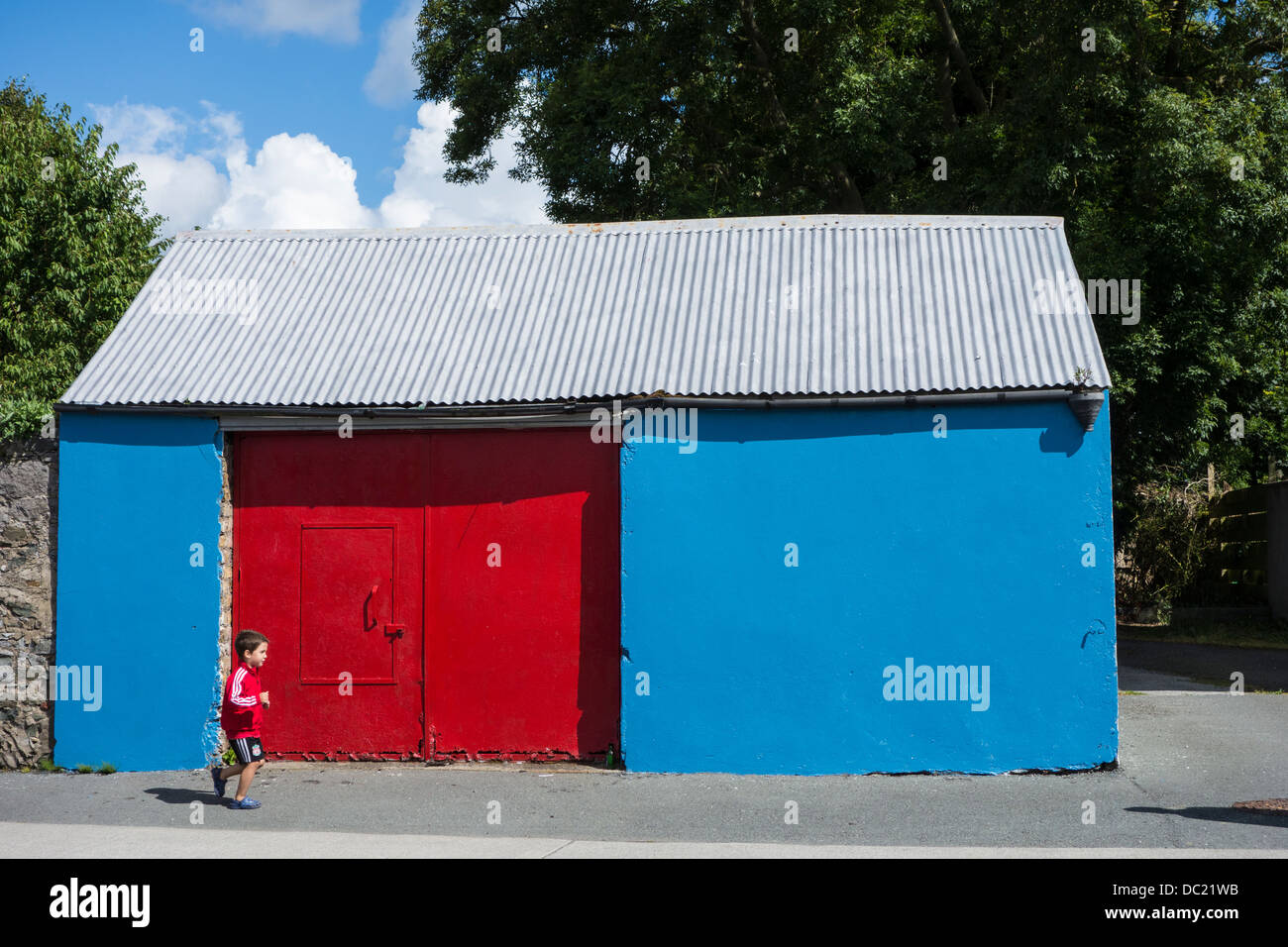 Yong child passing a brightly painted old shed,  red and blue - outside Dublin, Ireland Stock Photo