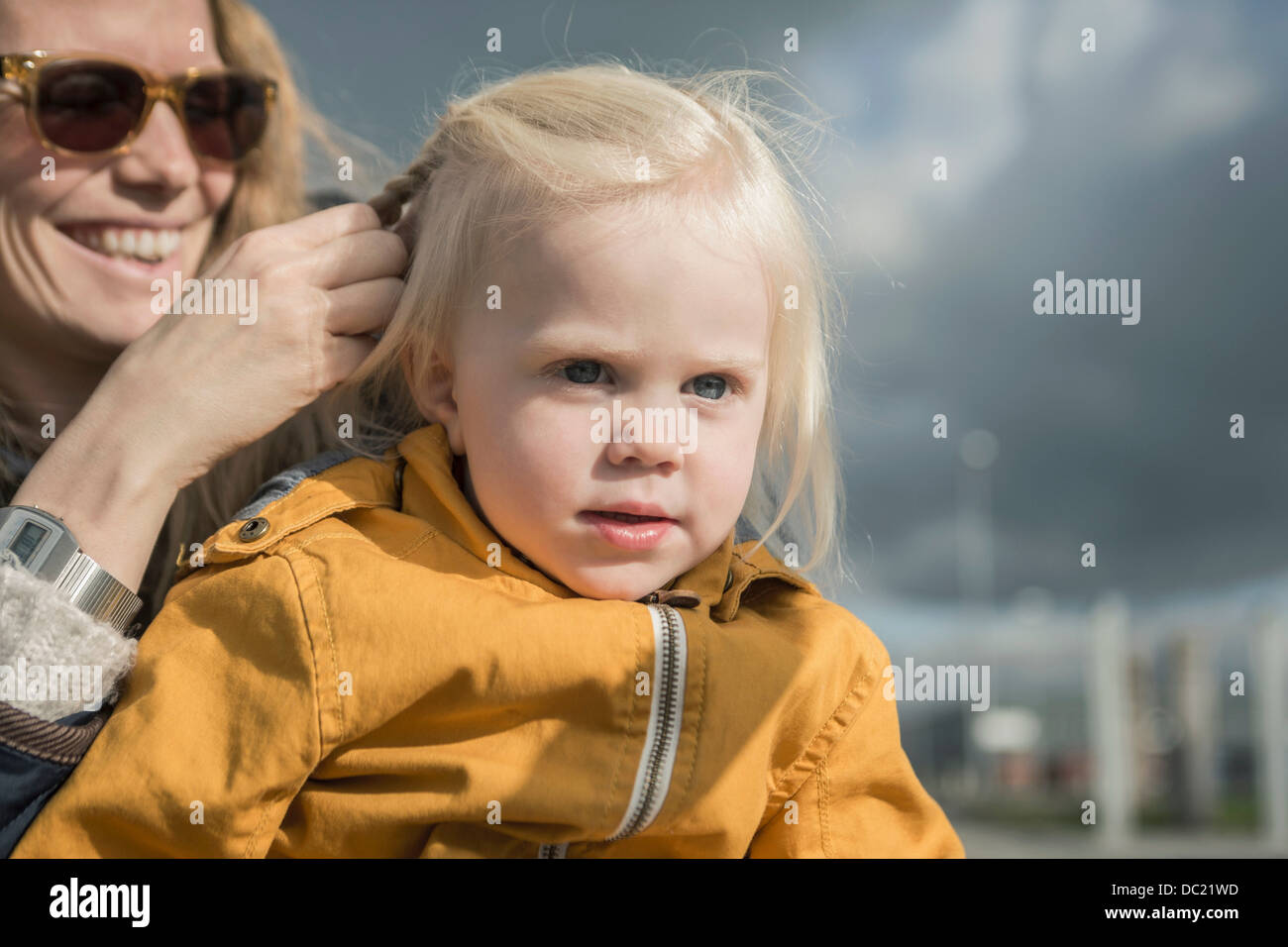 Outdoor portrait of mother braiding toddlers hair - Stock Image