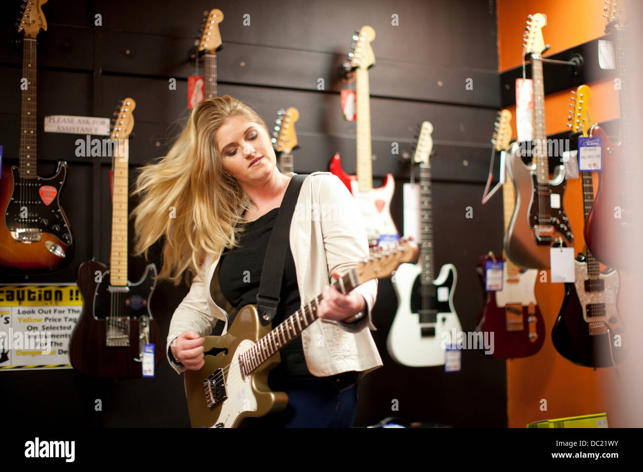Young woman testing guitar in music store Stock Photo