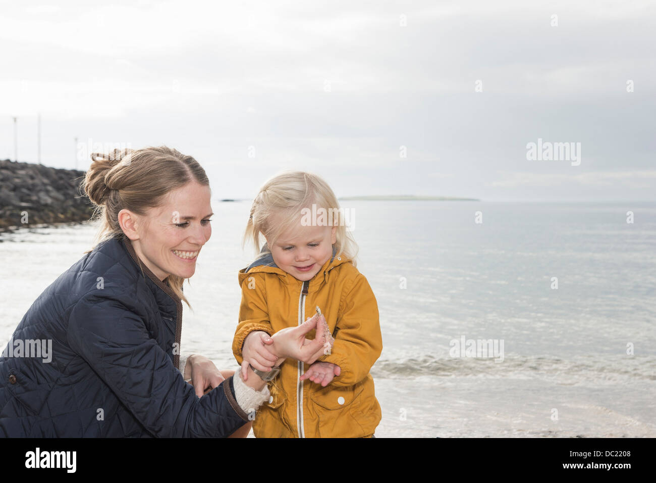 Mother and toddler exploring at coast - Stock Image