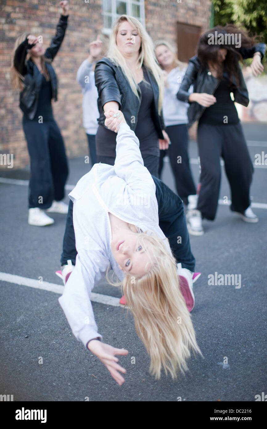 Girls dancing in carpark Stock Photo