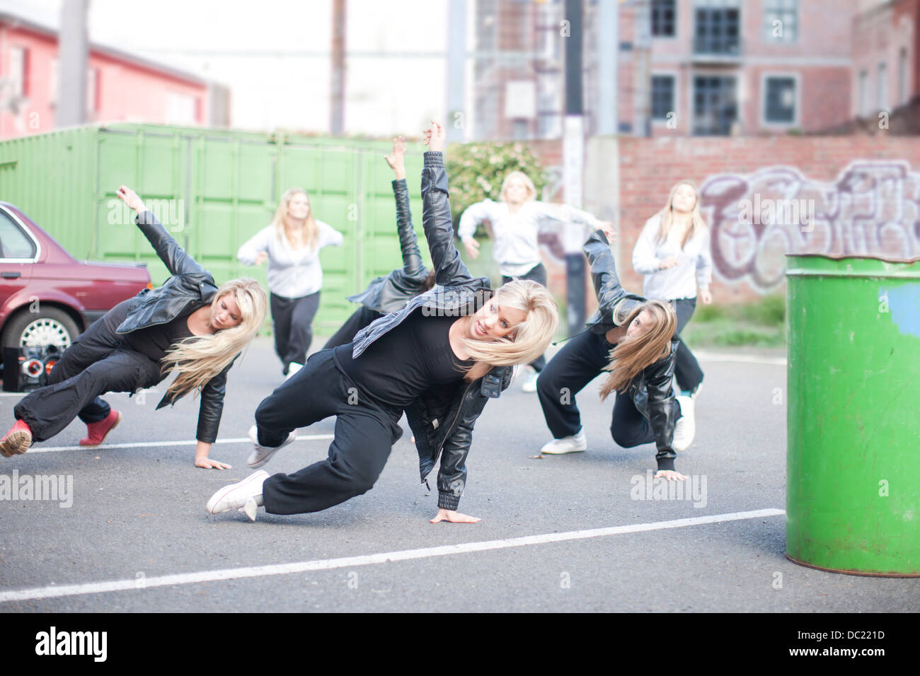 Girls practicing dance moves in carpark - Stock Image