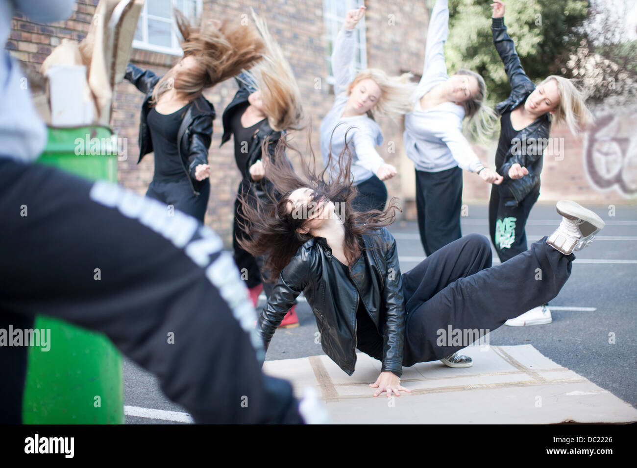 Group of girls breakdancing in carpark Stock Photo