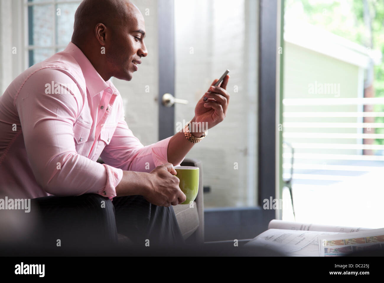 Mid adult man sitting on sofa looking at mobile phone Stock Photo