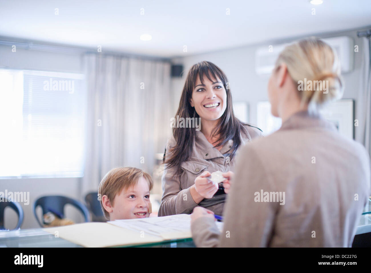 Mother and son making appointment at hospital reception - Stock Image