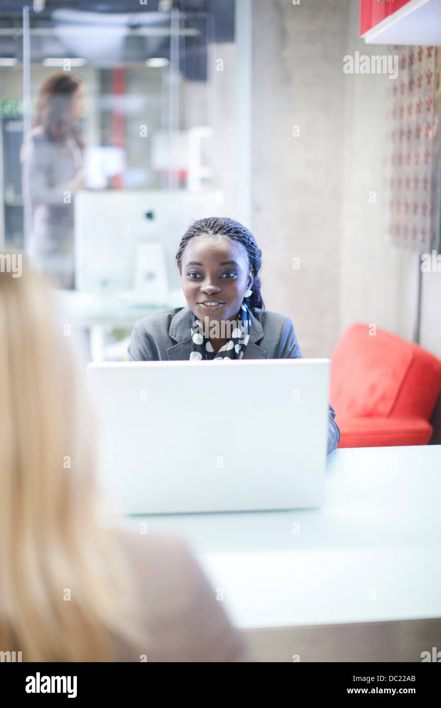 Office workers chatting at desk - Stock Image