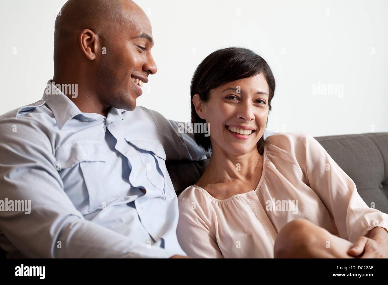 Couple relaxing on sofa, portrait - Stock Image