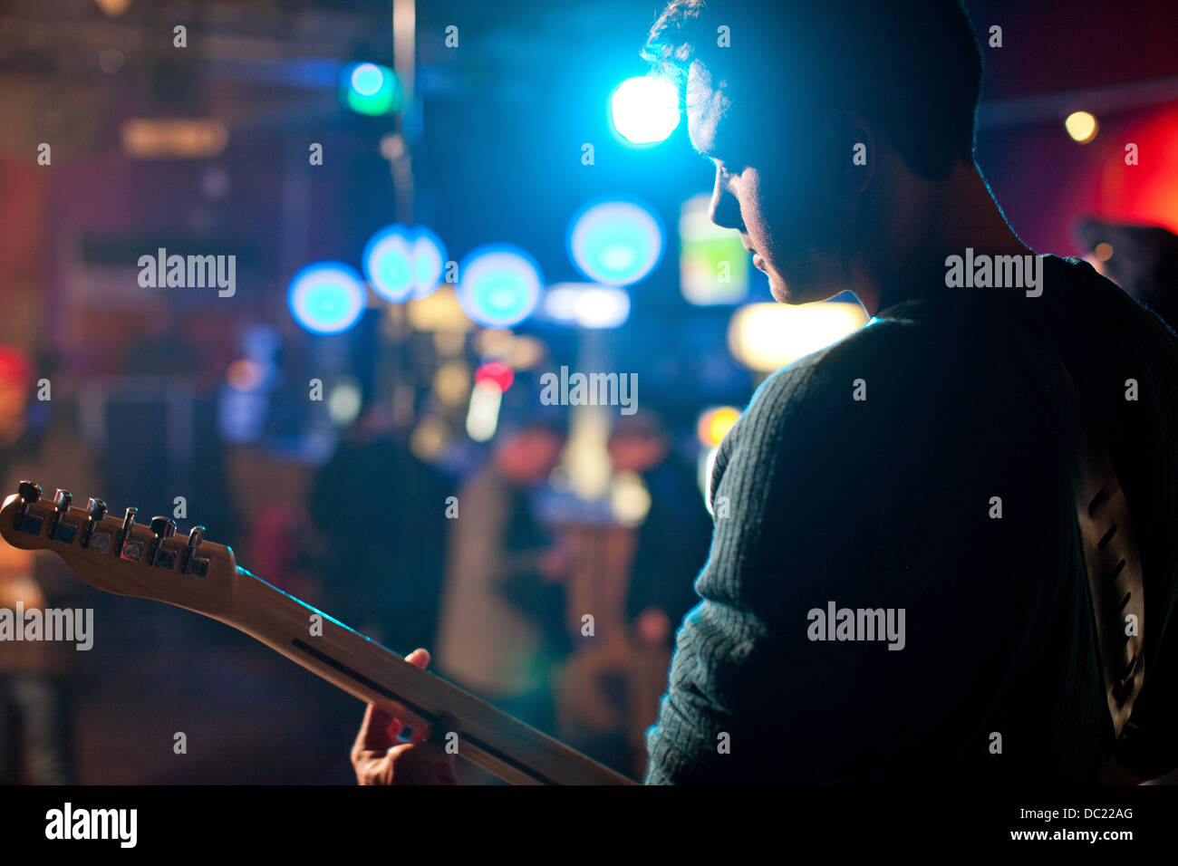 Man on stage playing guitar in nightclub - Stock Image