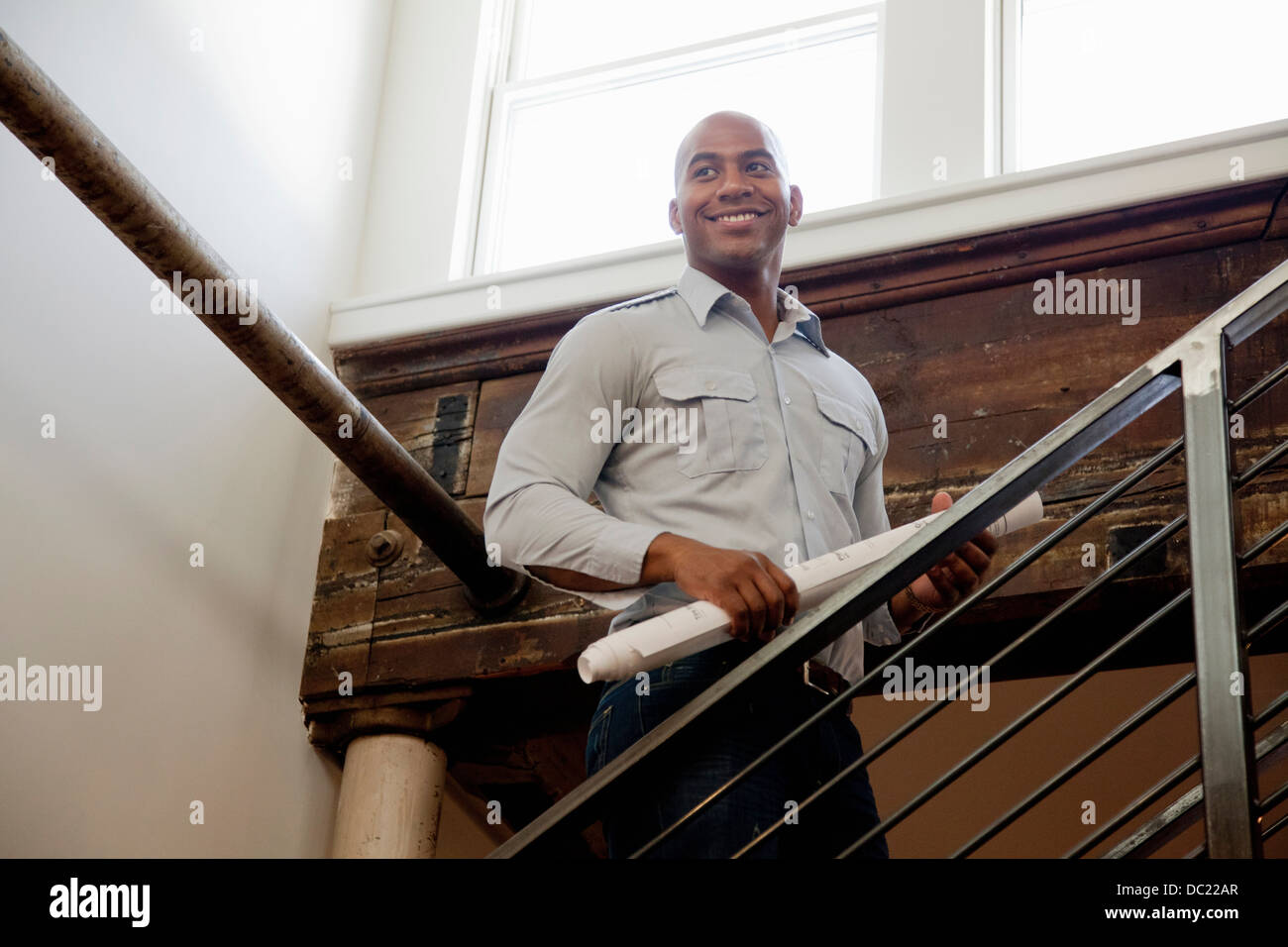 Mid adult man holding rolled up plans on staircase, smiling - Stock Image