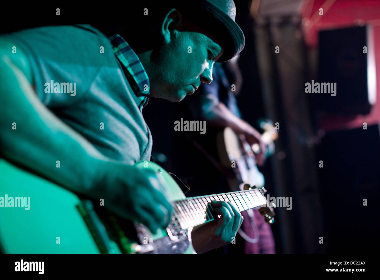 Man playing guitar on stage in nightclub - Stock Image