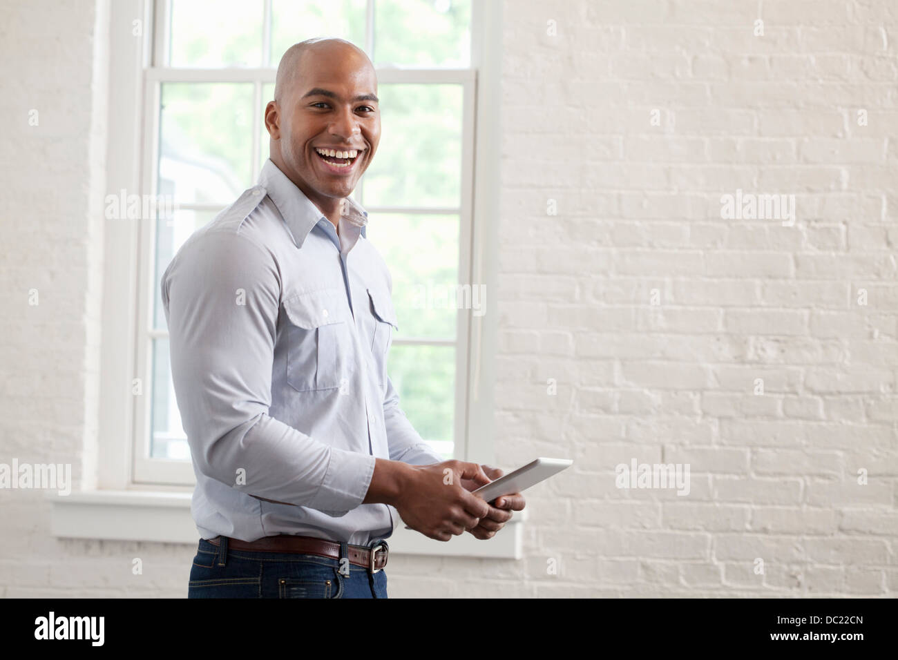 Mid adult office worker holding digital tablet and smiling, portrait - Stock Image