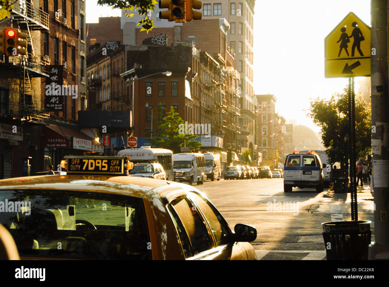 Sunlit taxi cab in street of Chinatown, Manhattan, New York, USA - Stock Image