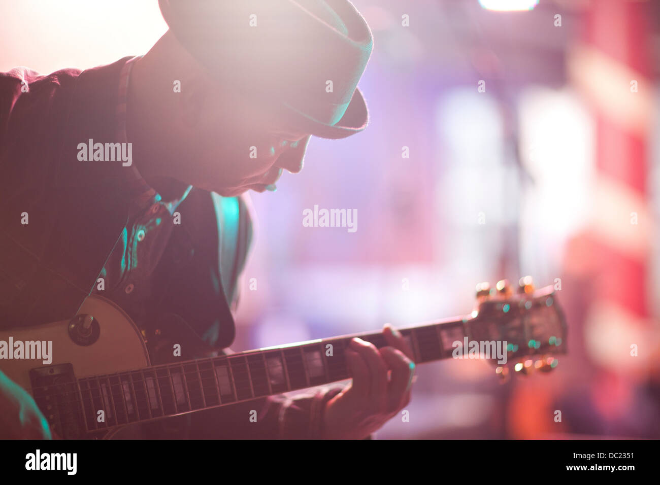 Close up mature man playing guitar on stage - Stock Image