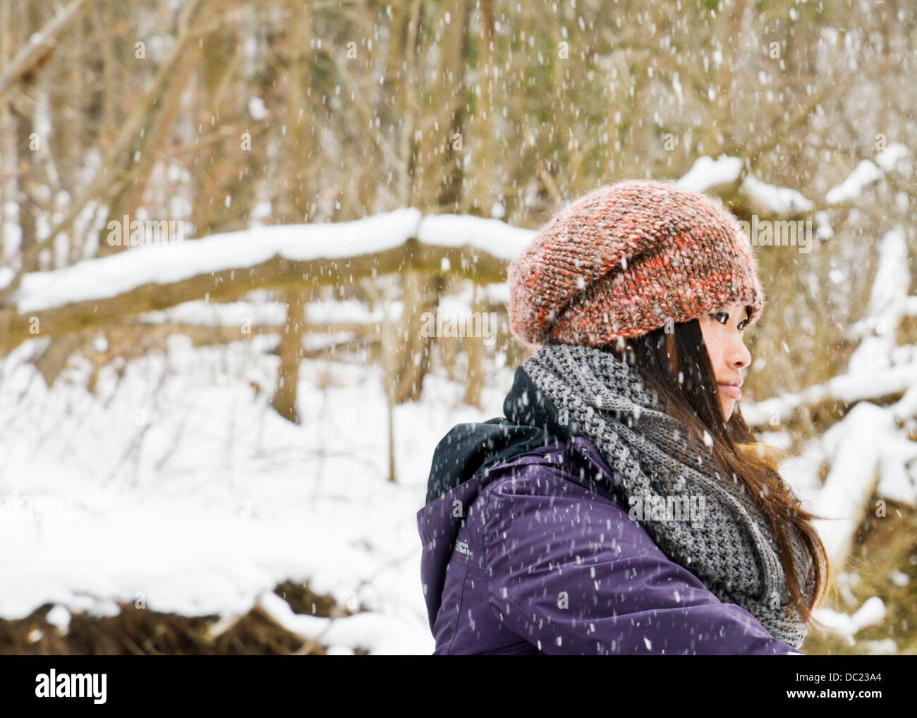 Young woman wearing knit hat and scarf in snow Stock Photo