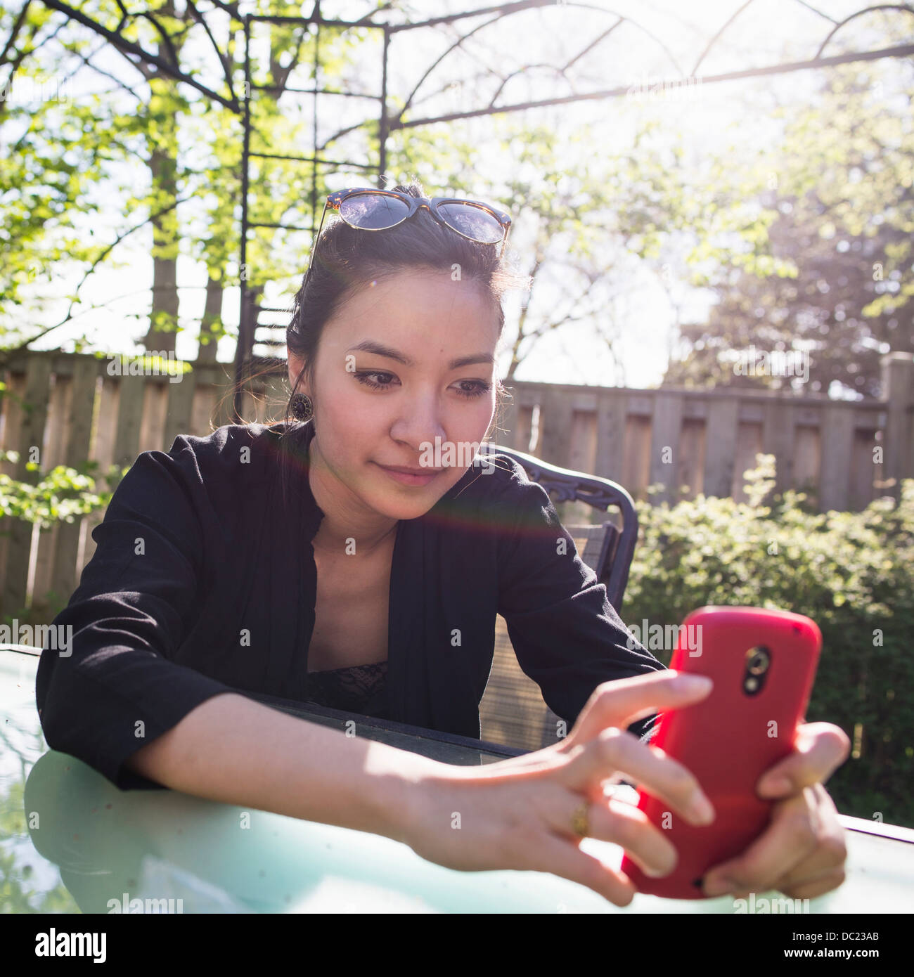 Young woman using red mobile phone outdoors - Stock Image