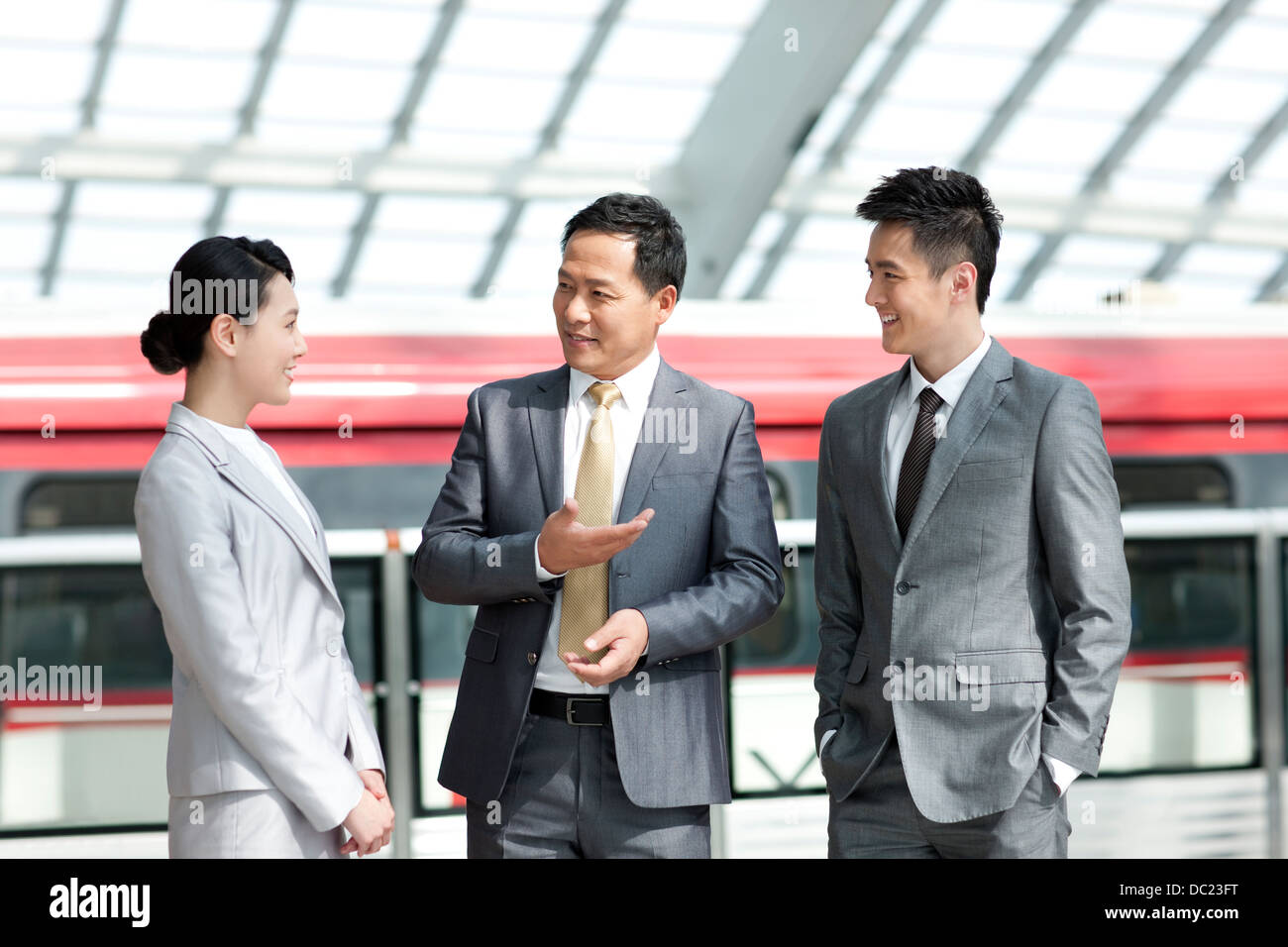 Chinese business persons talking at subway station Stock Photo