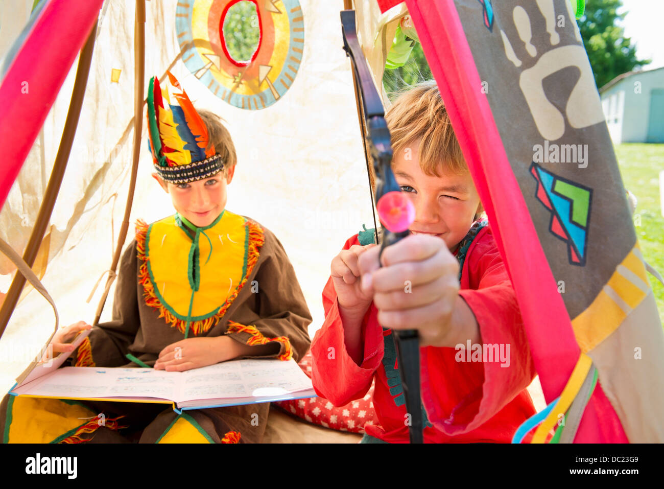 Brothers dressed in Native American costumes playing in teepee, portrait - Stock Image