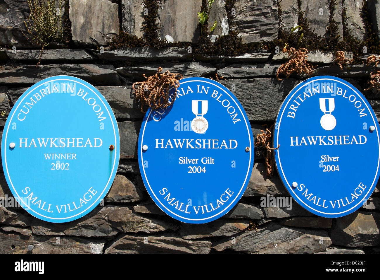 Plaques on a wall in the Beautiful Lakeland village of Hawkshead showing  success in Cumbria  and Britain in bloom - Stock Image