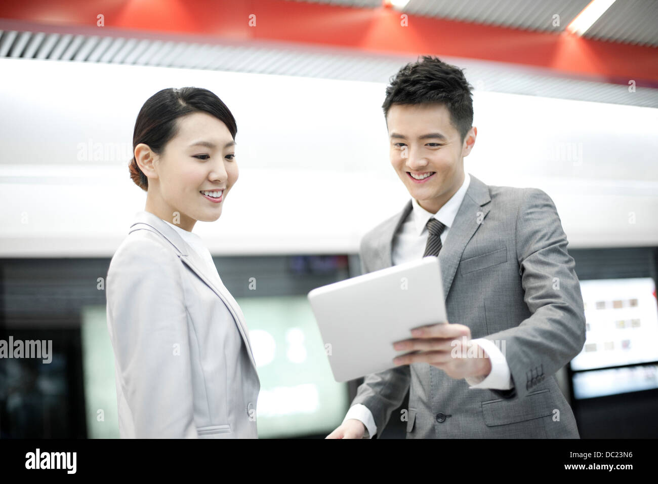 Young Chinese business partners with digital tablet on subway platform - Stock Image